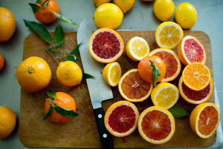 naranjas-y-limones-cortados-sobre-mesa